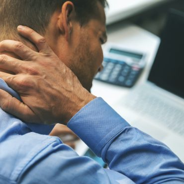 office syndrome - man suffering from neck and back pain while working with computer; blog: Neck Pain: Do You Need to See a Doctor?